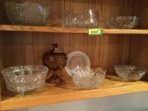 Two shelves of glassware/crystal-serving bowls, 8 inch plate, two moon and star pattern dishes, one anniversary jar and a candle holder