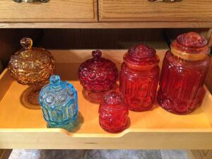 Red canisters, red covered candy jar, blue covered candy dish and Amber covered candy dish. Lid of one red canister is damaged