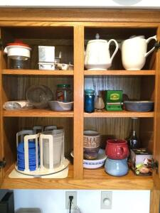 Contents of cabinet include Harbaugh pottery, vases, Lazy Susan with storage containers and lids, John Deere toothpick dispenser, salt or pepper shakers, soup mugs, multi grater, chopper, tea carafes and more