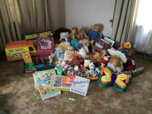 An assortment of stuffed animals, cars, tractors, Barbie bus, Barbie case, smash hockey game, puzzles, games and books.
