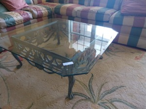 SET OF METAL FRAMED TABLES , ONE COFFEE TABLE AND ONE END TABLE , HEAVY HEAVY GLASS TOPS , FRAMES DO HAVE AN ORNATE LOOK AND ARE VERY WELL MADE.