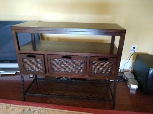 WOODEN TV STAND, APPROX 42 INCH LONG, DOES HAVE THE VERY POPULAR BASKET LOOK STORAGE DRAWERS. VERY NICE.