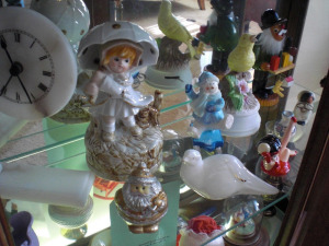CONTENTS OF FLOOR CURIO CABINET, 2 SHELVES OF MUSIC BOXES, CERAMICS, ALABASTER COLLECTIBLES