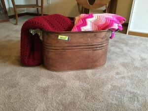 Antique copper boiler, one red afghan and one pink afghan