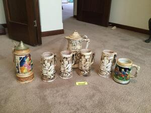 Four matching beer Steins with covered pitcher, pitcher handle is broken. Additional beer stein and stein that is also a music box