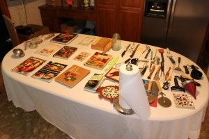 Miscellaneous cook books, pizza cutters, knives, measuring cups, misc. kitchen utensils