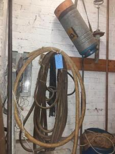 6 metal bars with tips at one end - set of torch hoses - metal cylinder hanging on wall. One solid bar with threaded end roughly 10 ft long