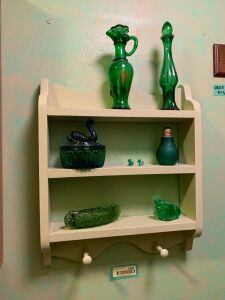 Wall shelf w/ pretty green decor, towel hanger w/ movable hooks and cabinet w/ its wicker baskets and contents. Cabinet measures 20x16x25 Bring tools to remove shelf from wall!
