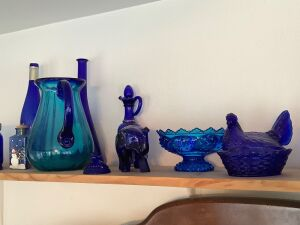 Beautiful blue glass includes Fenton candle holder, hen on nest, wall bud vase, elephant, bottles, Abbott and Costello glass