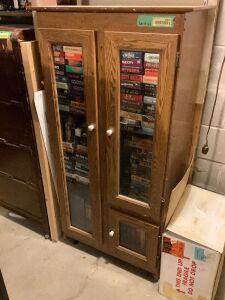 "Media cabinet with more than 100 VHS tapes and an extra box of VHS tapes - media canister measures 23""L x 15""W x 52""H"