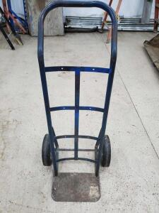 "Blue hand truck with solid tires. 20"" wide including tires, 45"" tall."