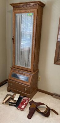 Eight gun cabinet with glass front and lower storage Has key, measures 23 x 18 x 80 Also included are gun cleaning accessories and leather holster
