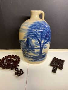 CAST IRON TRIVETS AND A STONEWARE JUG WITH BLUE SCENE
