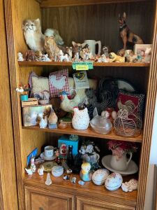 Large variety of figurines including one shelf of dogs, one shelf chicken themed and another one has some Amana, Iowa items and more