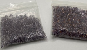 TWO SMALL BAGS OF WHAT APPEARED TO BE SMALL AMETHYST BEADS FOR JEWELRY MAKING.