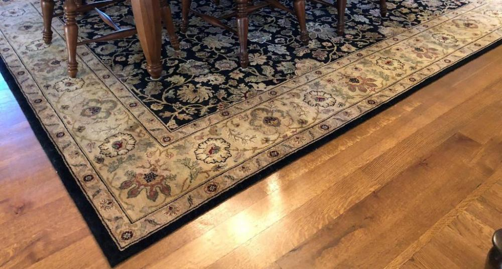 Area Rug In Colors Of Black Tan Green And Red